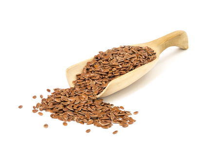 flaxseed: Wooden spoon floating over with linseed on white background