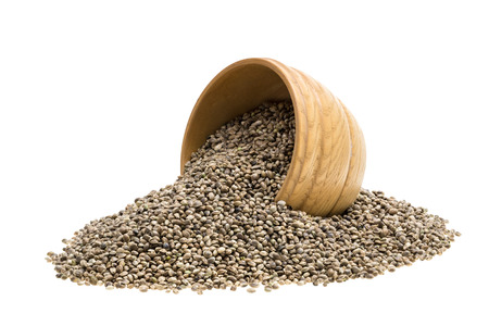 tipped: Wooden bowl with hemp seeds tipped over on white background
