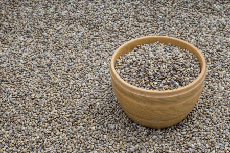 hemp hemp seed: Side view of wooden bowl with hemp seeds standing on a hemp seed background Stock Photo