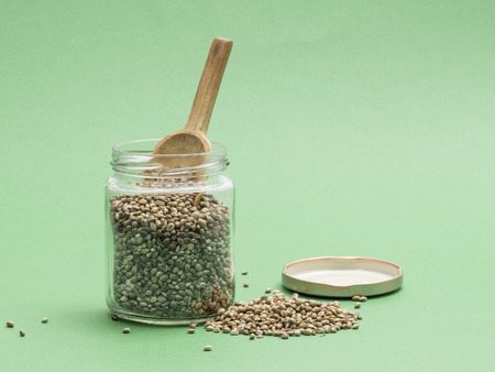 background green: Hemp seeds in a glass jar with a wooden spoon on a light green background seen from the side