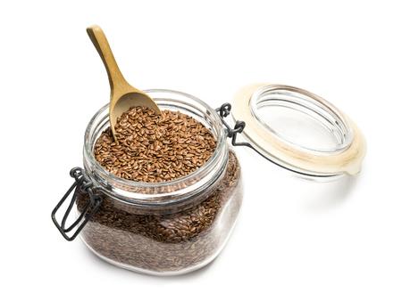 Lijnzaad of vlas in een glazen pot met deksel en houten lepel op een witte achtergrond