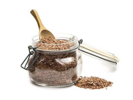 linseed: Side view of linseed or flax in a glass jar with lid and wooden spoon on white background Stock Photo