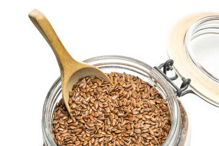 linseed: Close up of linseed or flax in a glass jar with lid and wooden spoon on white background