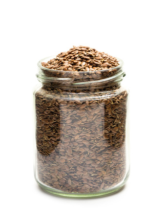 linseed: Side view of glass jar with linseed or flax on a white background Stock Photo
