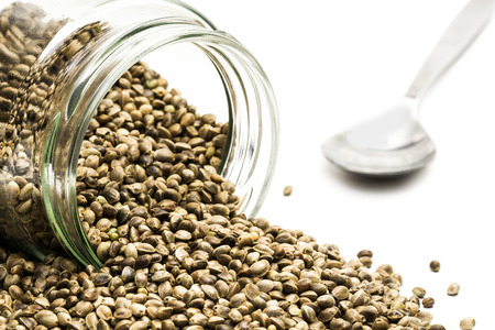 overturned: Close up of an overturned glass jar with hemp seeds and a metal spoon behind on white background
