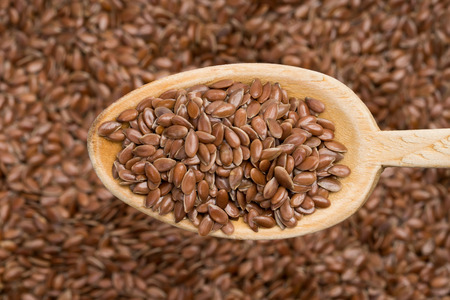 Wooden spoon with linseed coming from right seen from above over a linseed background Stock Photo