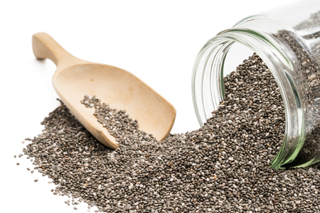Chia seeds spilled from an overturned glass jar with a wooden spoon in the background isolated on white