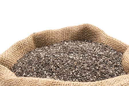 Chia seeds in a burlap sack on white background
