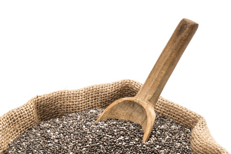 Chia seeds with a wooden spoon in a burlap sack on white background close up