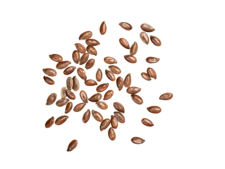 Some linseeds or flax seed spread out on white background seen from above