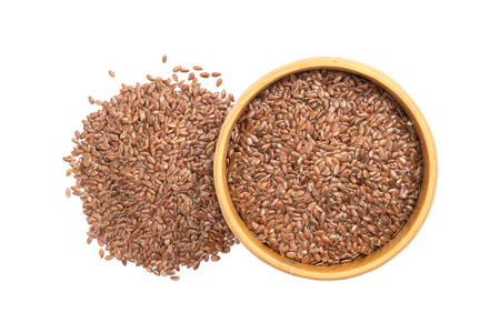 Linseed or flax seed in a wooden bowl and a pile next to it seen from above isolated on white background