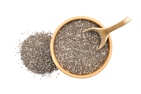 Chia seeds in a wooden bowl with spoon and a small pile next to it seen from above isolated on white background