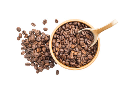 Coffee beans in a wooden bowl with a spoon and a pile next to it seen from above isolated on white background Stock Photo