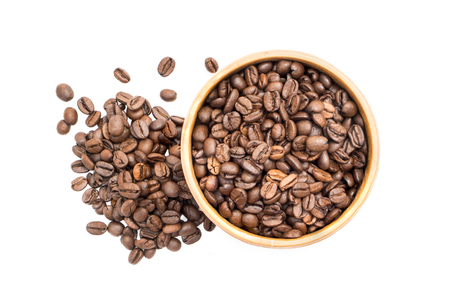 Coffee beans in a wooden bowl with a pile next to it seen from above isolated on white background