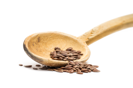 Linseed or flax seed on a tilted wooden spoon seen low angle isolated on white background