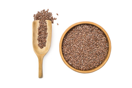 Linseed or flax seed in a wooden bowl and a spoon to the left seen from above isolated on white background
