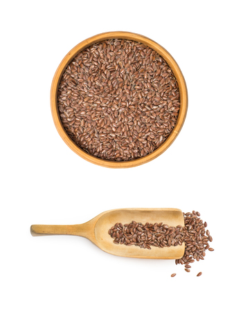 Linseed or flax seed in a wooden bowl and a spoon under it seen from above isolated on white background
