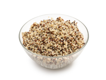 Cooked mixed quinoa seeds in a round glass bowl seen obliquely from above and isolated on white background Stock Photo