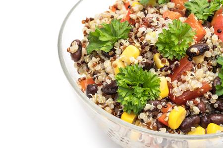 Cerca del recipiente de vidrio con ensalada de quinua con pimiento rojo, maíz, tomate y frijoles negros, cubierto con perejil y aislado sobre fondo blanco. Foto de archivo