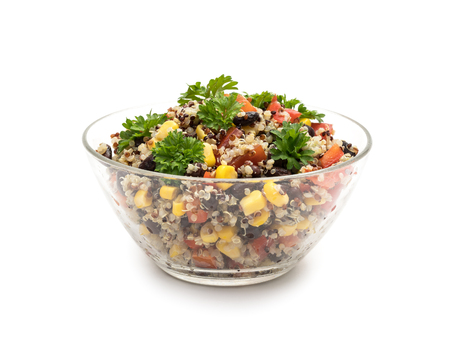 Side view of glass bowl with quinoa salad with red pepper, corn, tomato and black beans, topped with parsley and isolated on white background Stock Photo