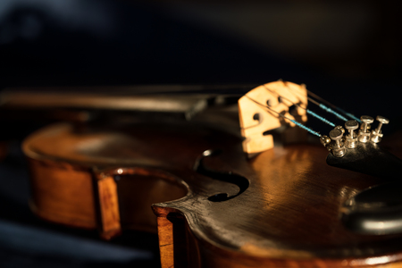 Close up of an old violin with selective focus and dark background
