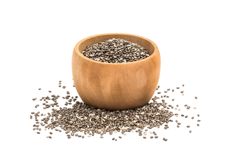 Chia seeds in small wooden bowl with some spilled in front of it seen from the side and isolated on white background Stock Photo
