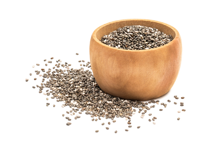 Chia seeds in small wooden bowl with some spilled next to it seen from the side and isolated on white background Stock Photo