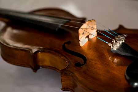 Close up of an old violin with selective focus and grey background