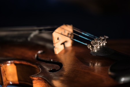 Close up of an old violin with selective focus at the fine tuners on dark background