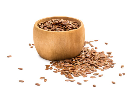 Small wooden bowl with linseeds or flax seeds seen from the side with some spilled in front and right and isolated on white background