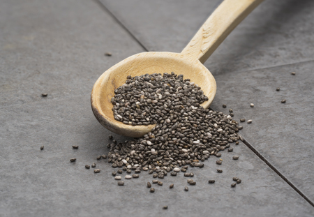 Close up of chia seeds on a wooden spoon seen from the front on a gray tile background