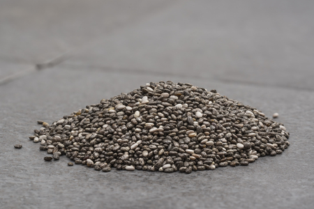 Pile of chia seeds on a grey tile background