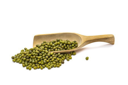 Mung beans on a wooden spoon seen obliquely from the side and isolated on white background