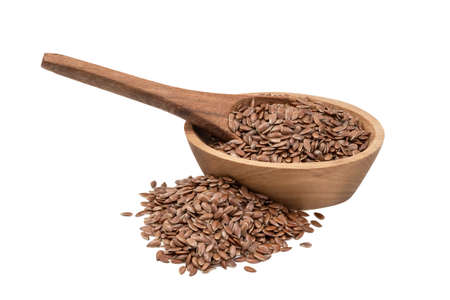 Linseeds or flax seed in a small oval wooden bowl with a spoon and pile next to it seen obliquely from the side and isolated on white background Foto de archivo