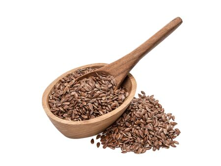 Linseeds or flax seed in a small oval wooden bowl with a spoon and pile next to it seen obliquely from front and above and isolated on white background Stock fotó