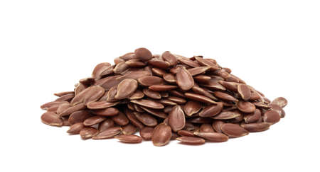Close up of small pile of linseed or flax seed seen fron the side and isolated on white with shadows