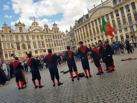 Brussels, Belgium. Juy, 2016. A group of portuguese university students playing instruments and singing at the Grand Place of Brussels, waving a great flag of Portugal. Members of university tuna Editorial