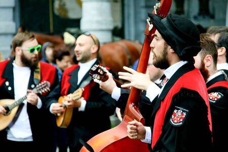 Brussels, Belgium. Juy, 2016. A young member of a group of portuguese university students playing instruments and singing at the Grand Place of Brussels. Members of university tuna