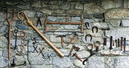 northern spain: Old tools exposed over an stone wall at Erill La Vall, a narrow, steep-sided valley and a small municipality in the province of Lleida, in the autonomous community of Catalonia, northern Spain   Stock Photo