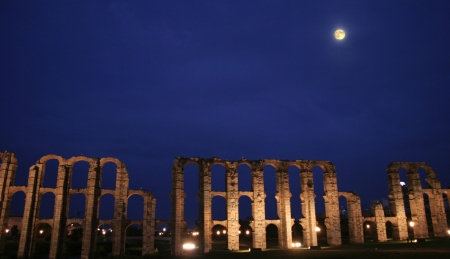 badajoz: Wide view of roman aqueduct of Merida at moonlight Stock Photo