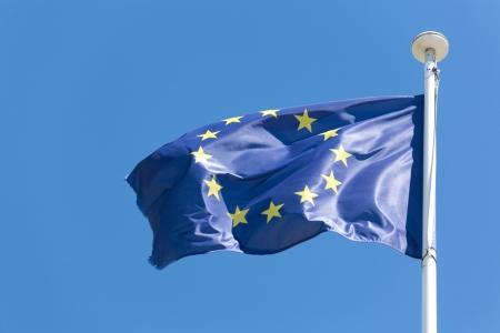 brisk: European Union flag fluttering in a brisk breeze against a blue sky