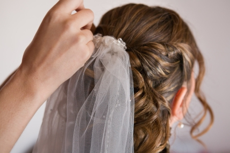 Placing the pin on a wedding hairstyle of bride with white veil  photo