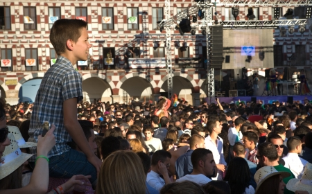 bisexuals: A young man watches the crowd from the shoulders of another Editorial