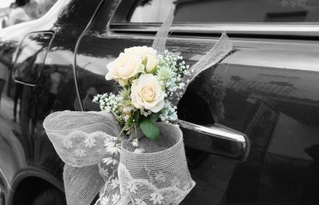 Puerta del coche negro de la boda con flores y el arco blanco
