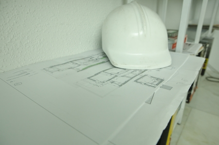 Rolls of architectural drawings and white construction helmet photo