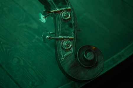 rehearsal: Neck of Cello with keys over the wooden stage before jazz concert Stock Photo