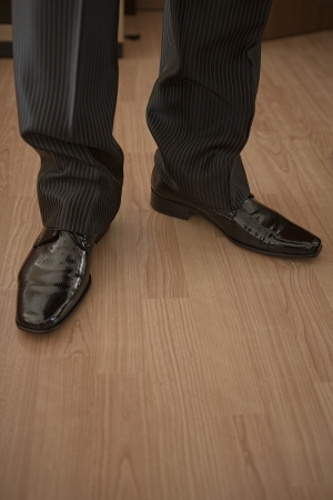 The groom black shinny shoe over wooden surface photo