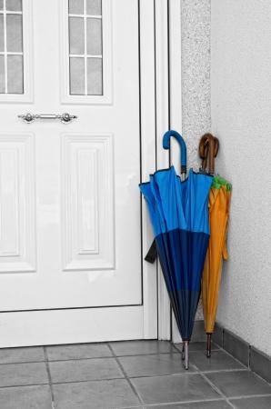 Few colorful umbrellas standing on an new brand white door Standard-Bild