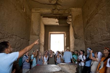 LUXOR, Egipto - 19 de julio Una guía con un grupo de turistas en el templo de Karnak en 19 de julio 2010 en Luxor, Egipto