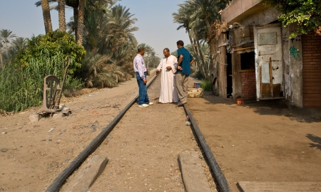DASHUR, EGYPT - JUL 21  Three man talking on the railroad tracks  Not exactly the smartest thing to do  Dashur, Egypt near the royal necropolis of Dahshur, on July 21, 2010, Dashur, Egypt